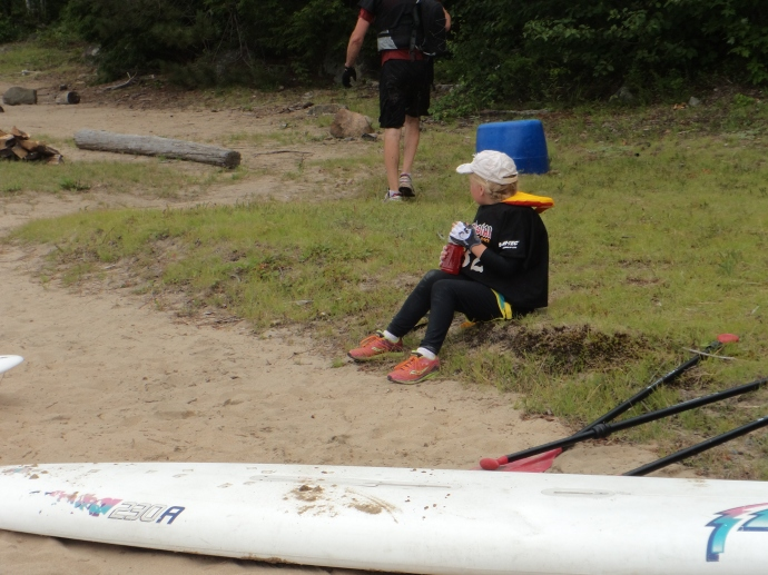 A younster waiting for her Dad to paddle in.
